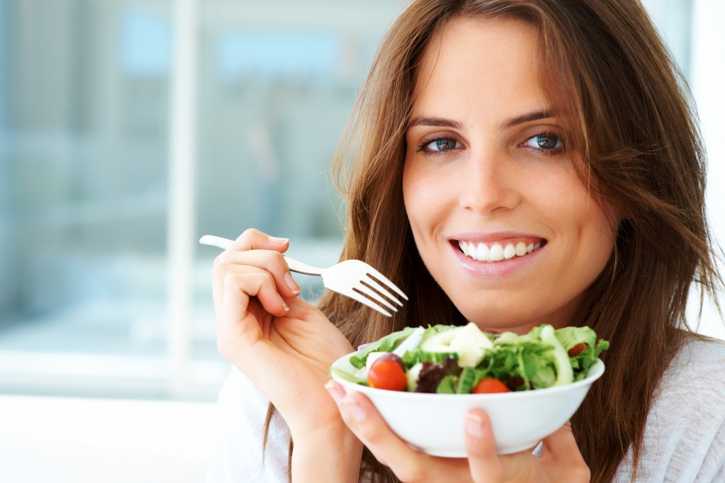 An attractive young woman eating fruit salad