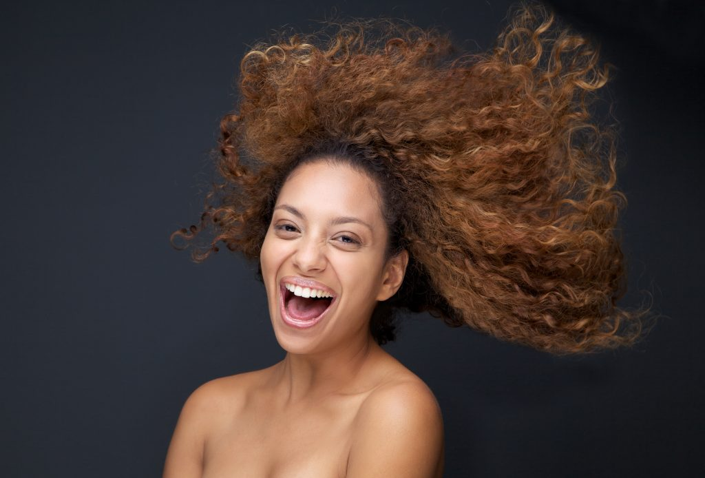 Close up portrait of an attractive young woman laughing with hair blowing